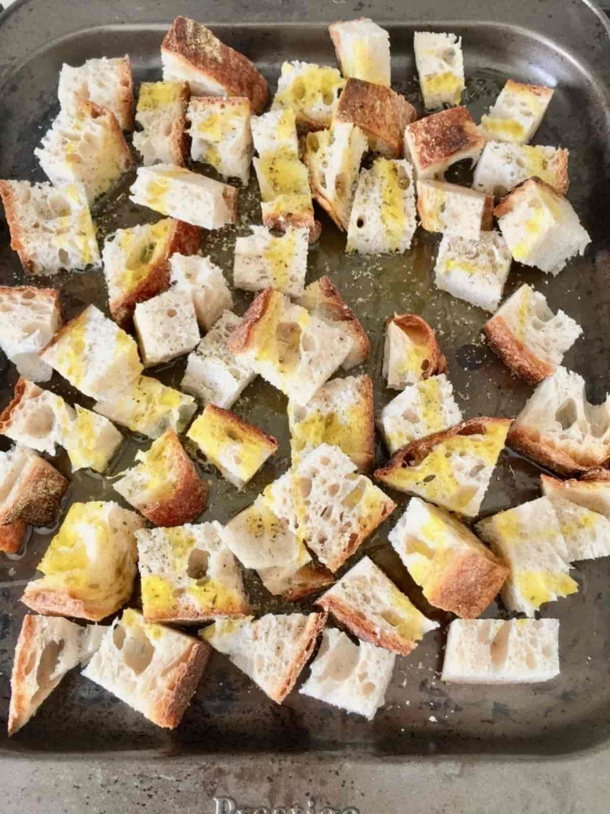 Chunks of bread sprinkled with oil & seasoning on a baking tray.