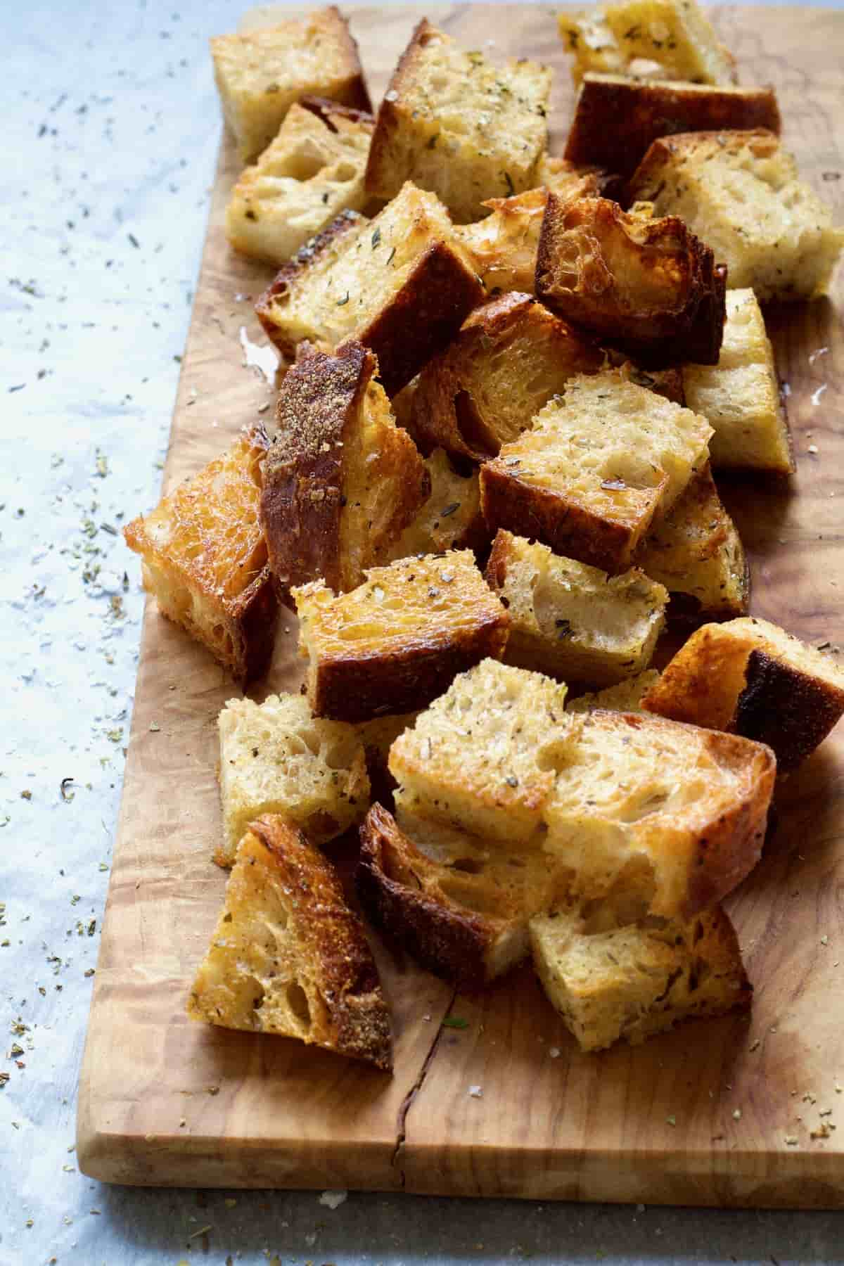 Homemade croutons piled up on a wooden board.