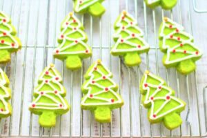 Christmas tree shaped cookies on a cooling rack.