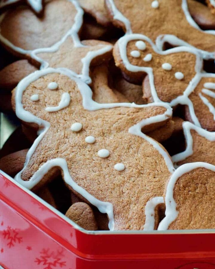 Close up of gingerbread man in a tin with other biscuits.