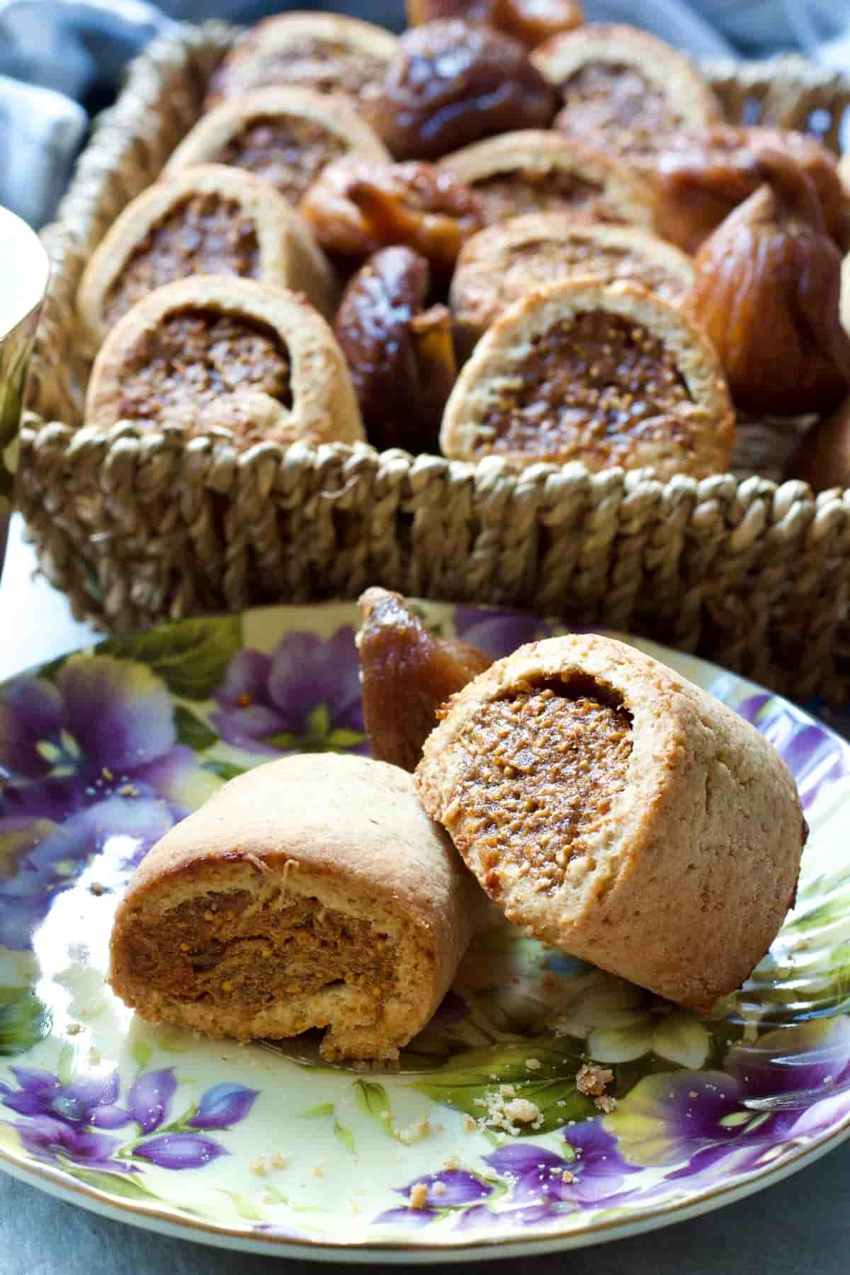 Two fig rolls on a plate with basket full of fig rolls behind.