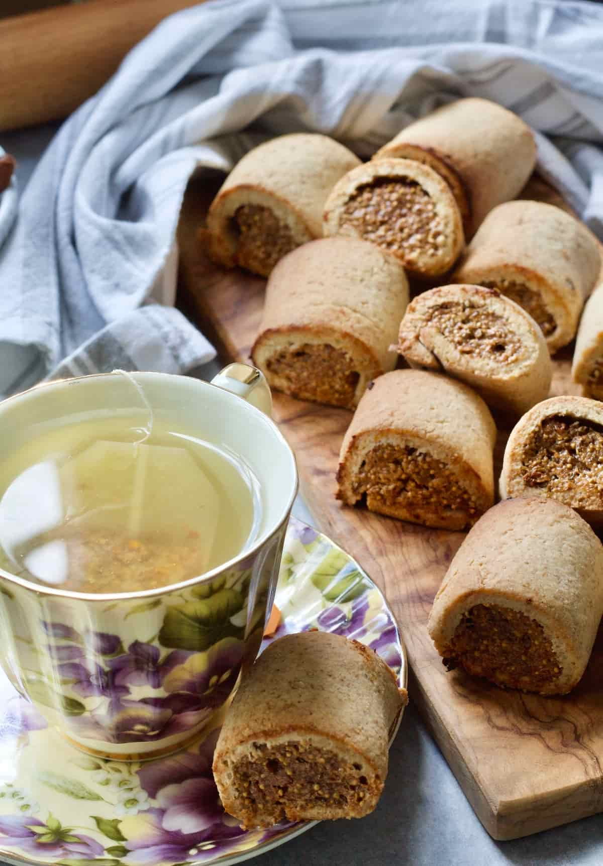 Fig roll on a saucer next to a cup of tea and more on a board.