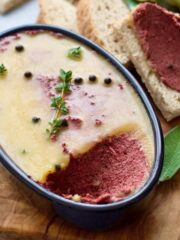 Mushroom and walnut pâté in an oval dish with thyme & peppercorns.