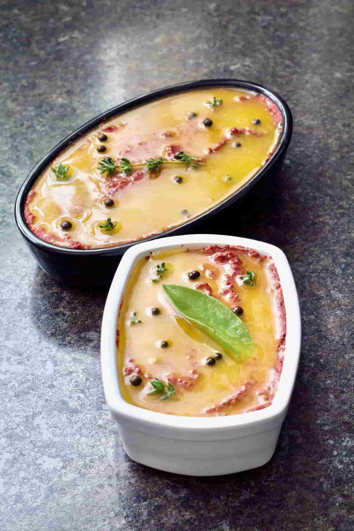 Mushroom and walnut pâté in two dishes, garnished with herbs and melted butter.
