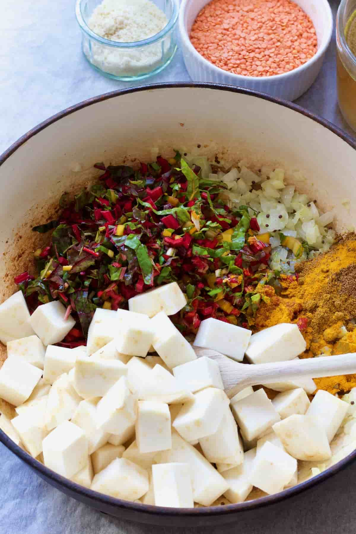 Pot with celeriac cubes, chard stalks, onion & spices.