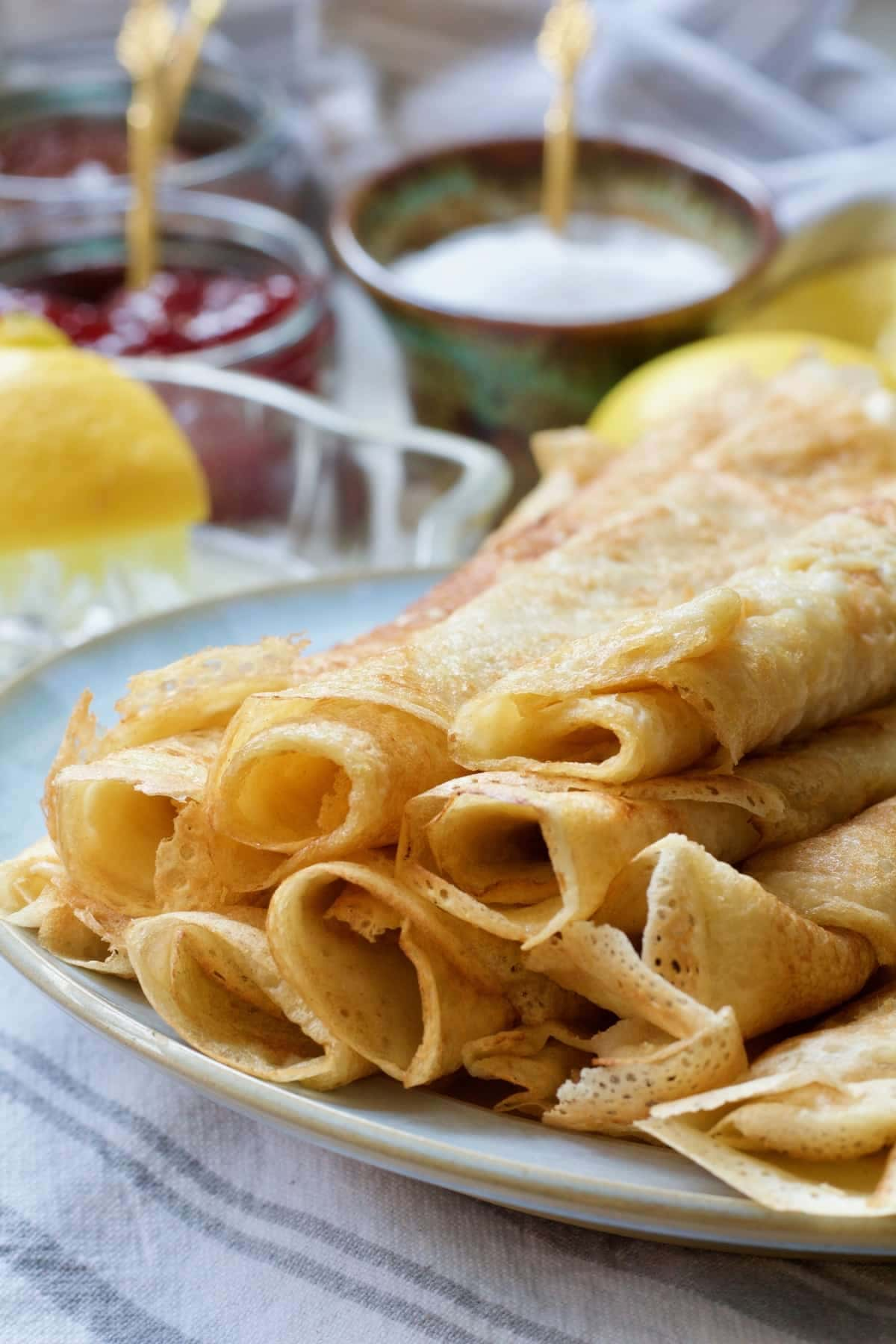 Close up of rolled vegan crepes on a plate.