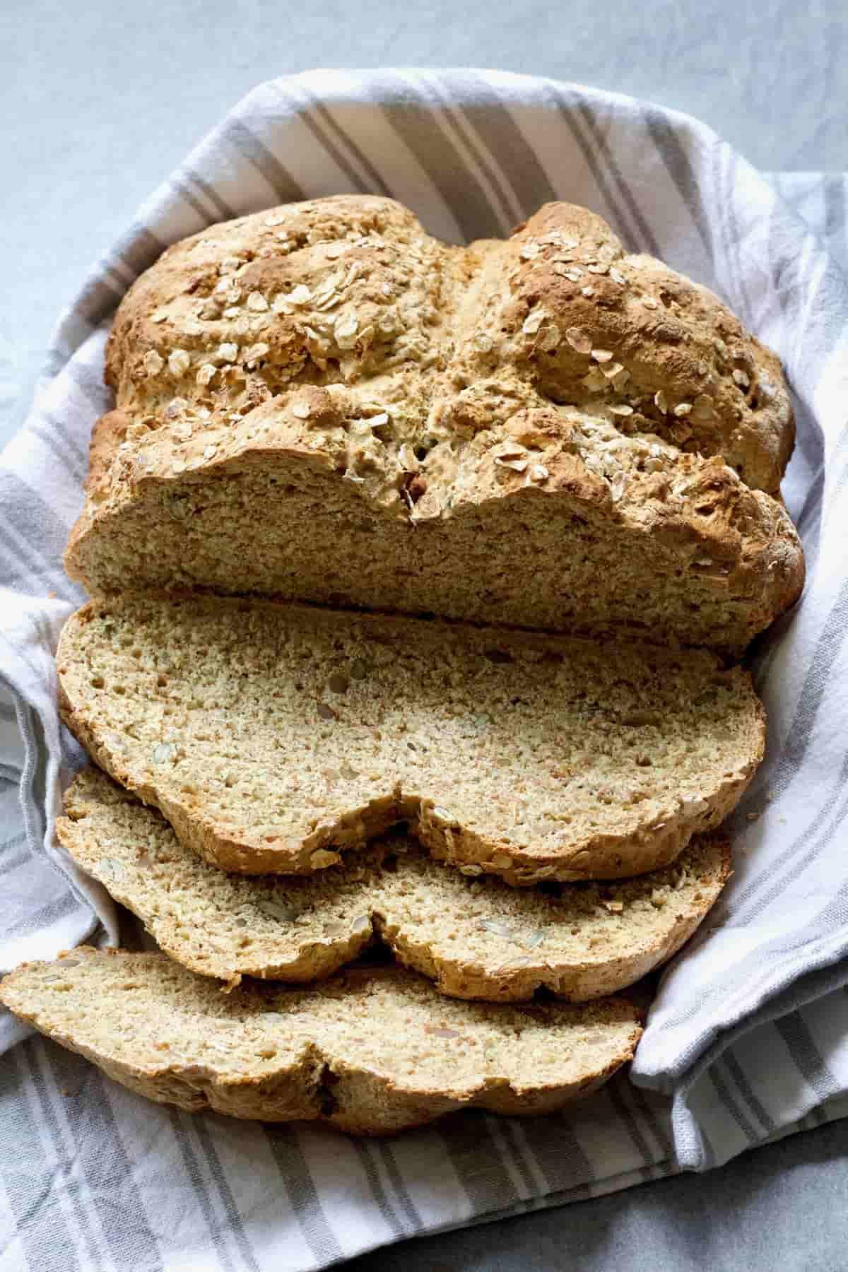 Loaf of vegan soda bread with few slices cut.