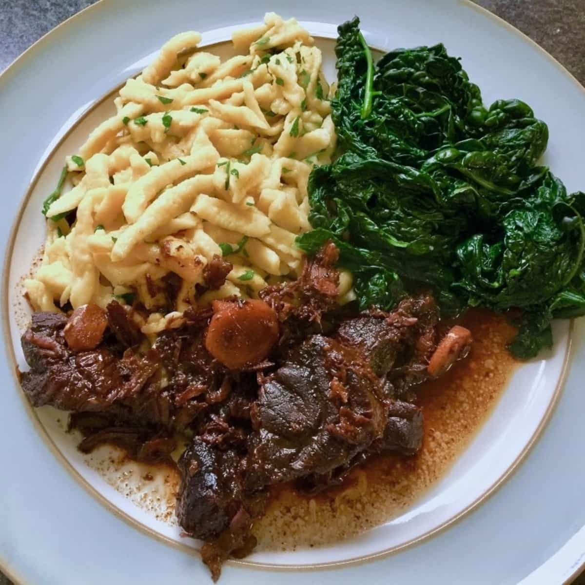 Chinese beef with soy and ginger, noodles and kale on a plate.