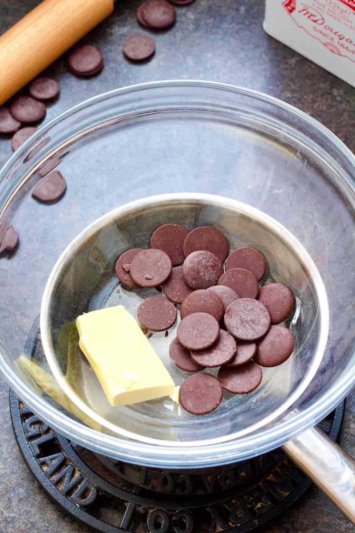 Chocolate buttons & vegan butter in a bowl over a pan.