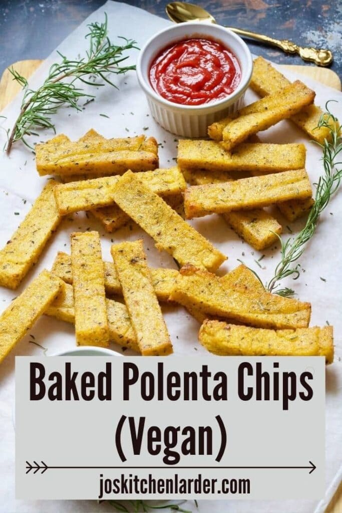 Polenta chips on a board with rosemary and bowl of ketchup.