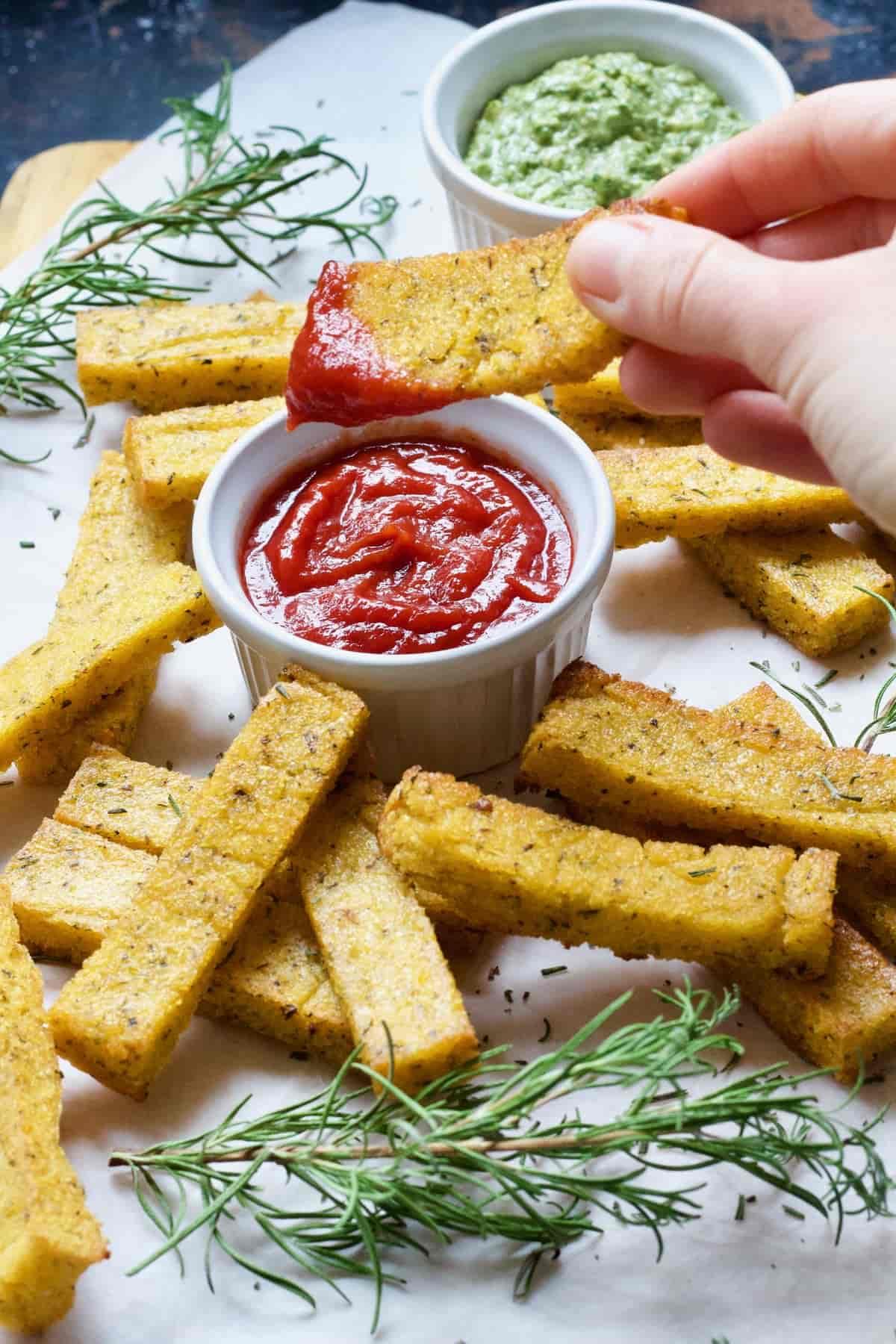 Hand dipping polenta chip in ketchup.