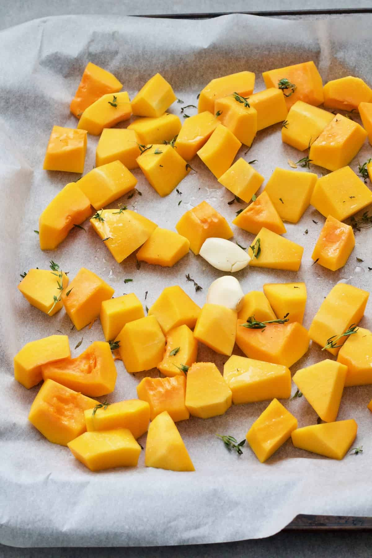 Chunks of butternut squash on a tray with 2 garlic cloves.