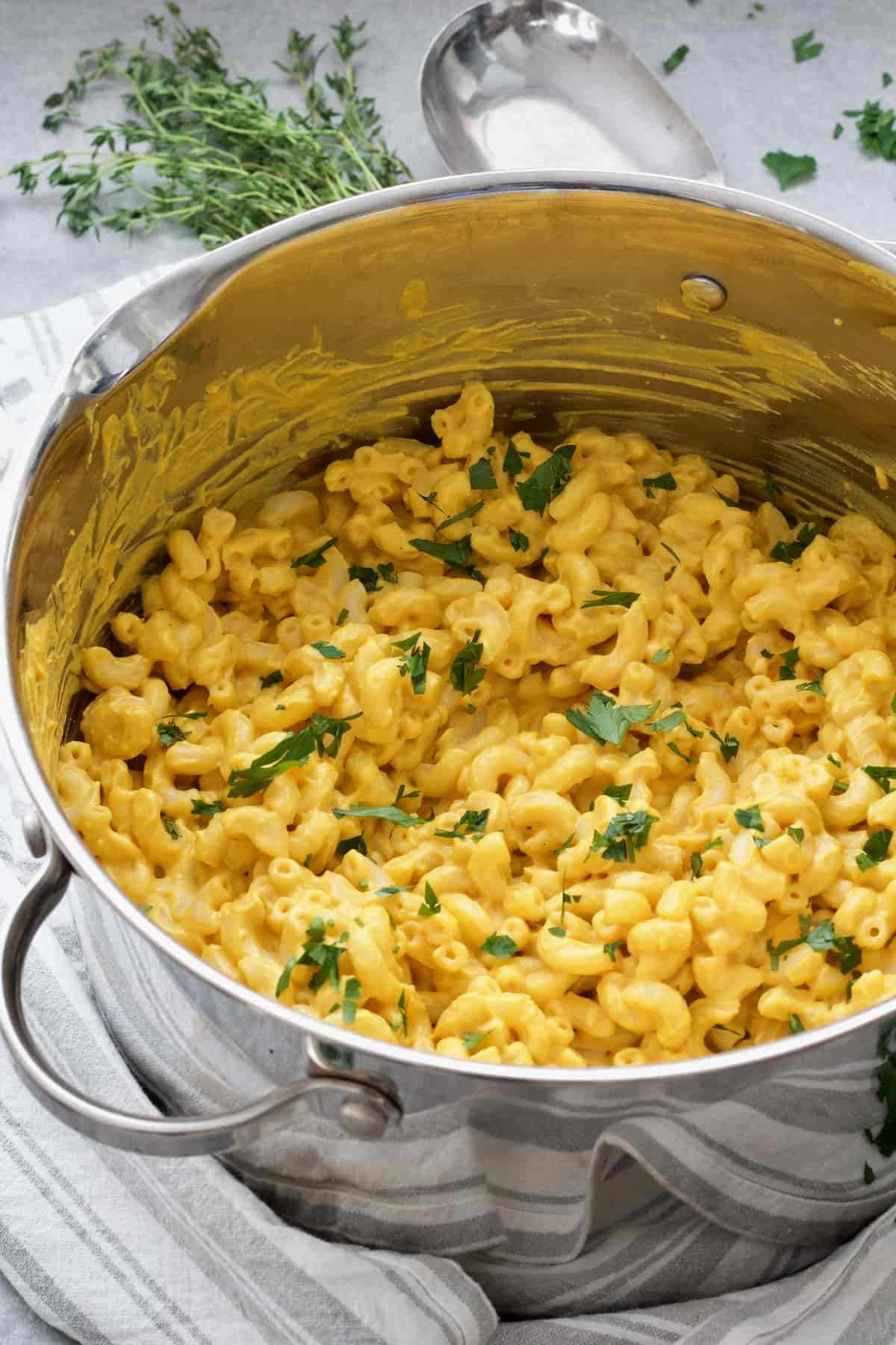 Pot with ready mac and cheese with parsley garnish.