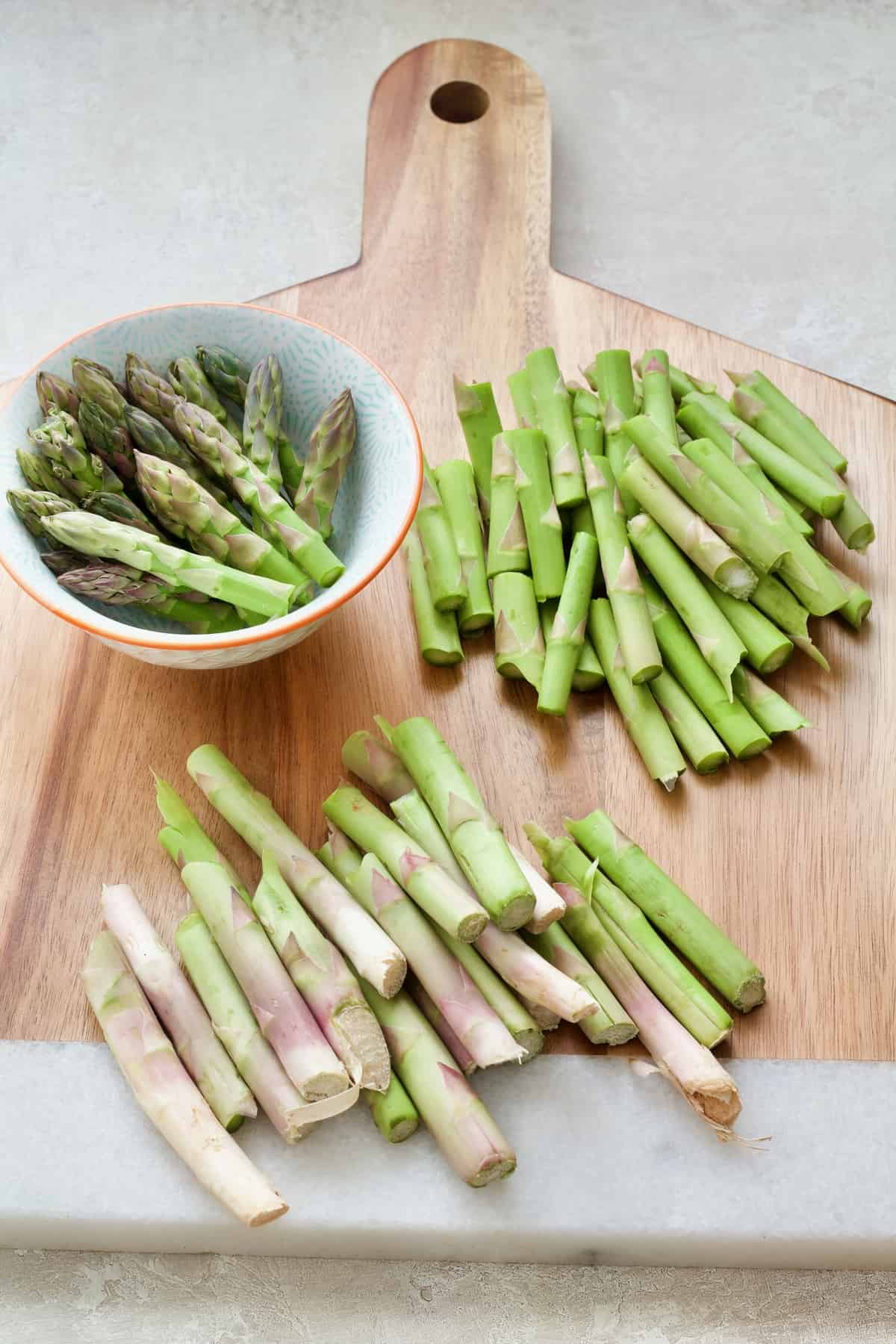 Prepared asparagus on wooden board.