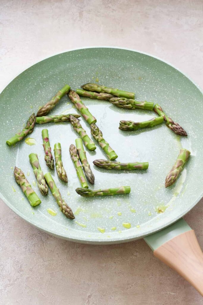 Asparagus tips in the frying pan.