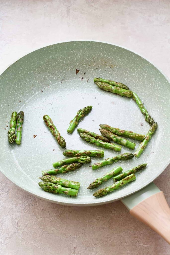Fried asparagus tips in the pan.