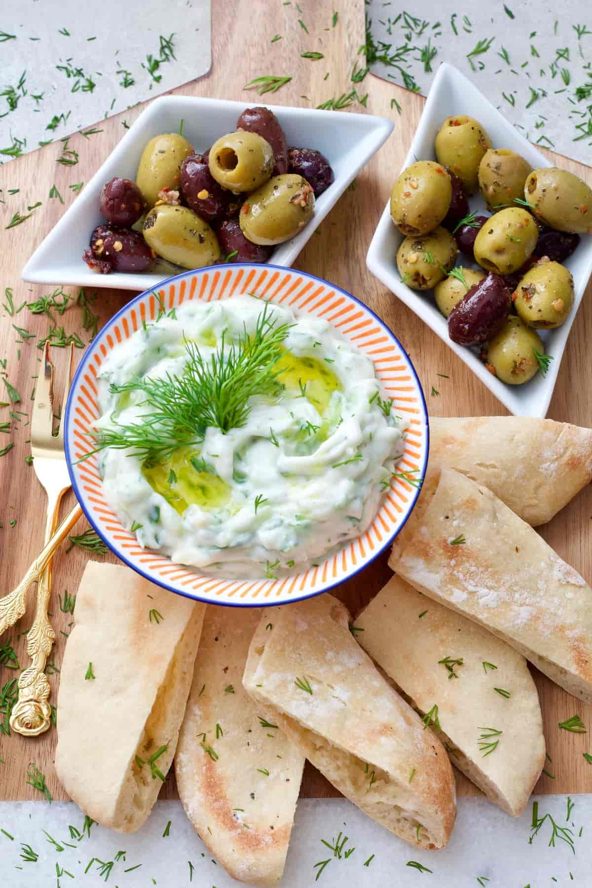 Dip in a bowl, olives & pita bread on a board.