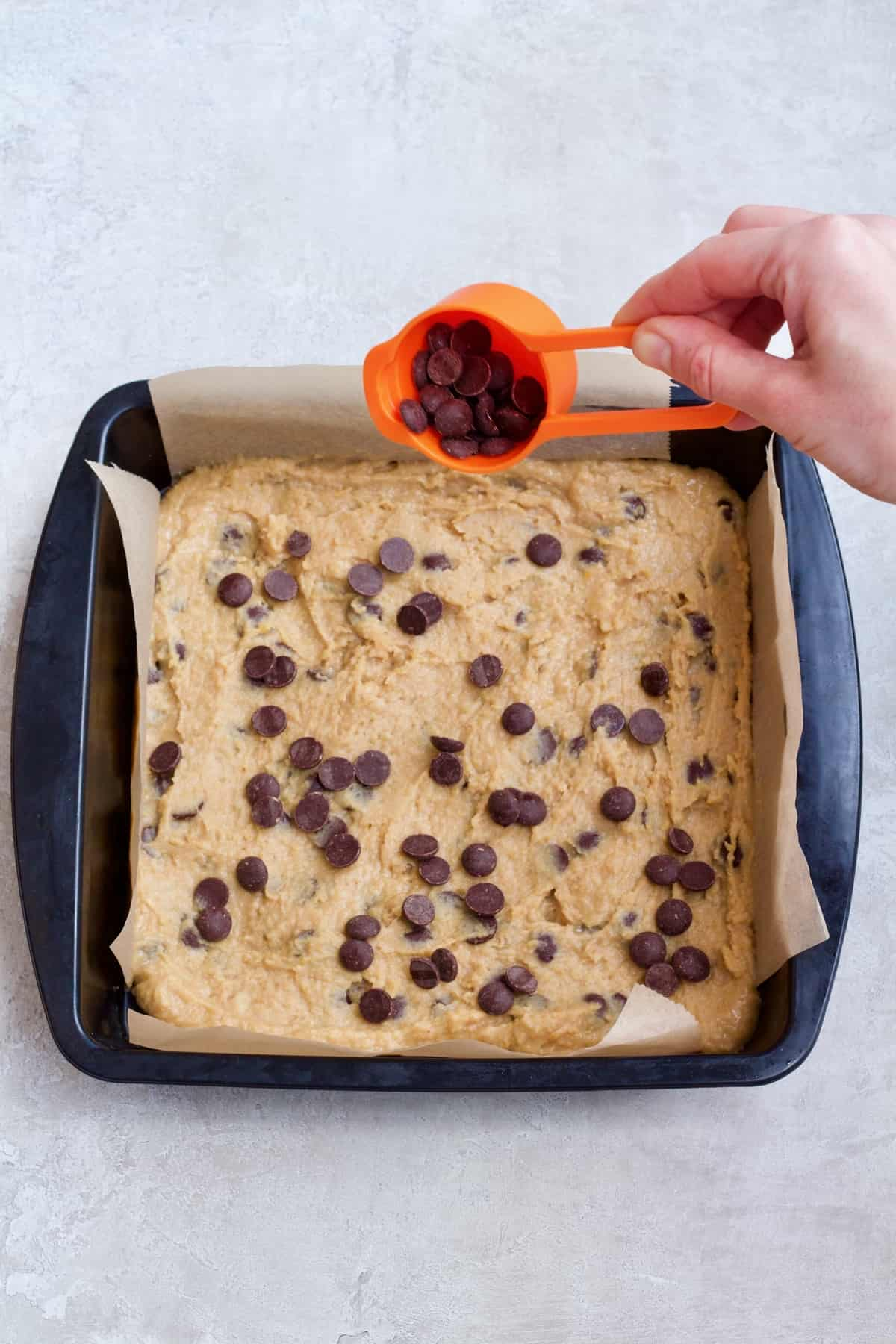 Hand sprinkling chocolate chips onto unbaked chickpea blondies.