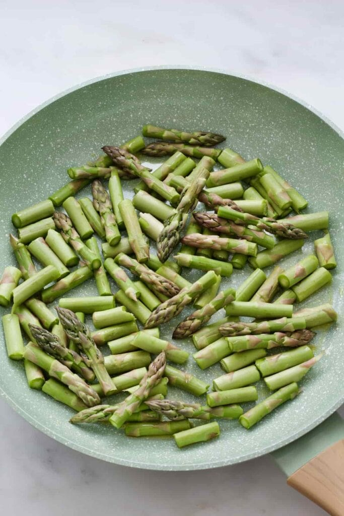 Fresh asparagus pieces in a pan before frying.