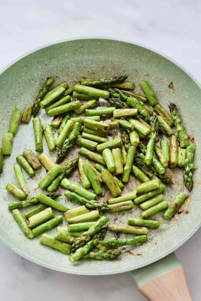 Fried asparagus pieces in a pan.