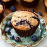 Vegan blueberry muffin on a plate with blueberries around it.