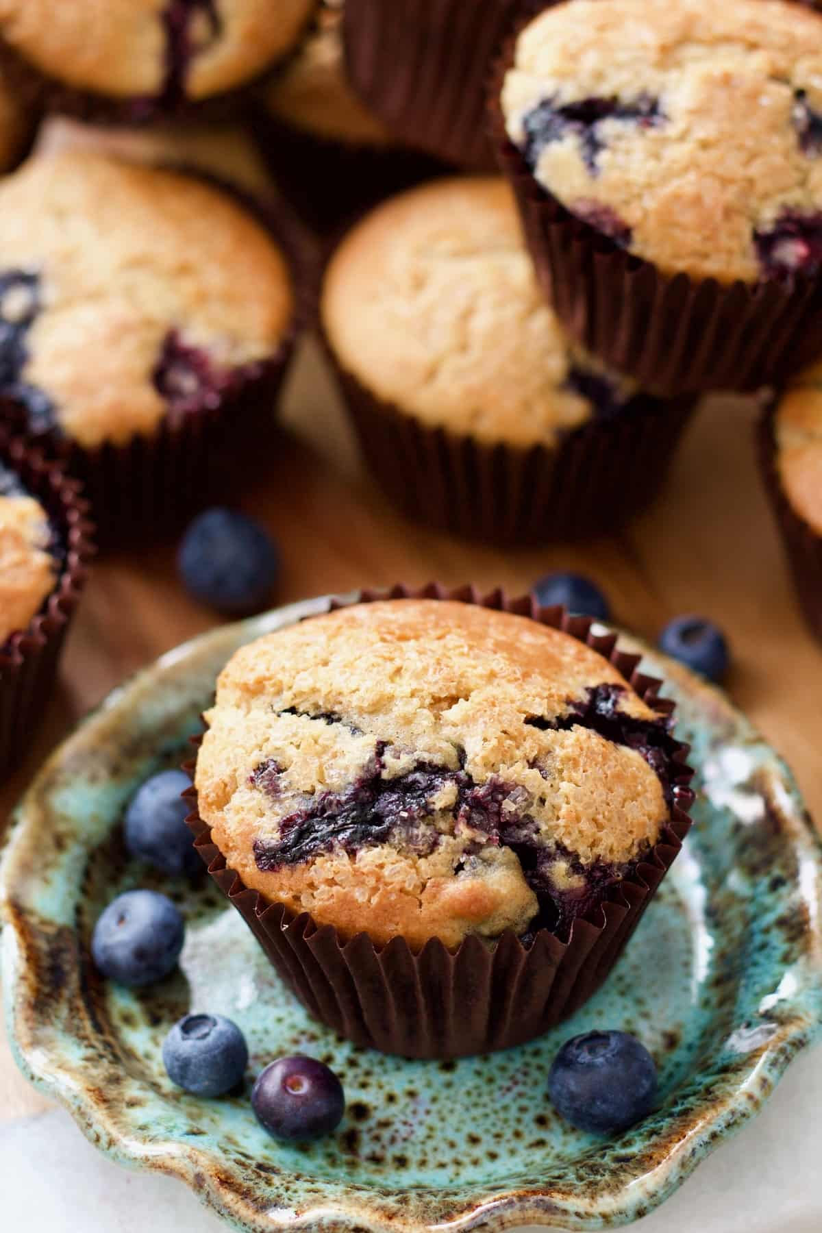 Blueberry muffin on a plate with more muffins behind it.
