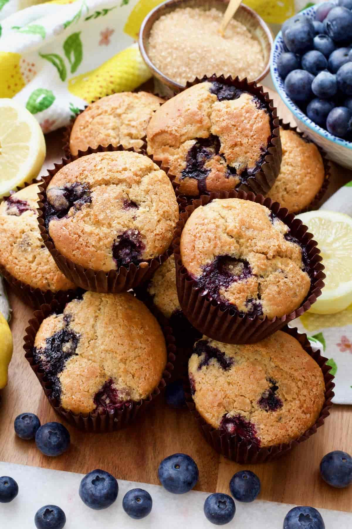 Blueberry muffins piled up on a board.