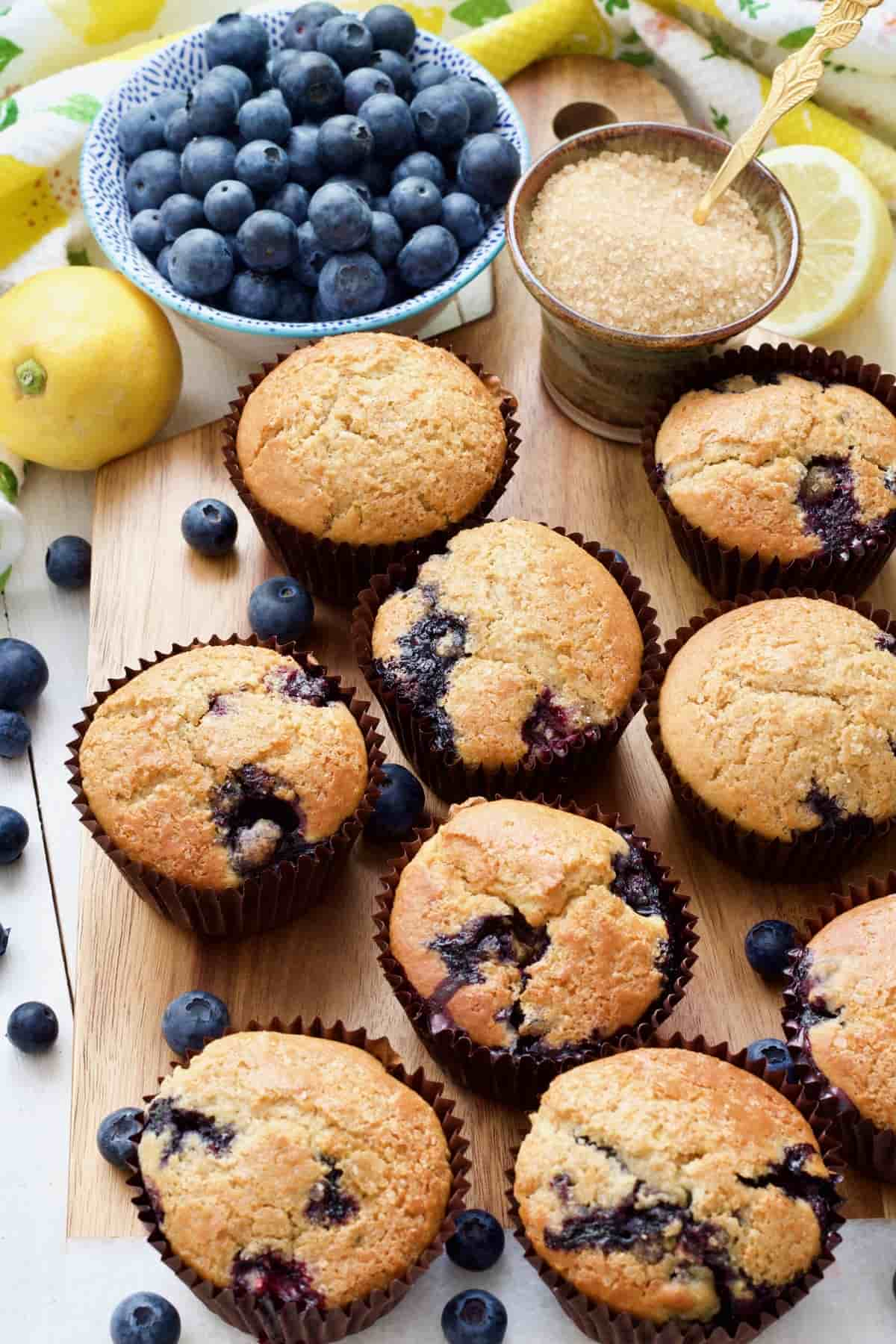 Muffins, bowl with blueberries, bowl with sugar & lemons.