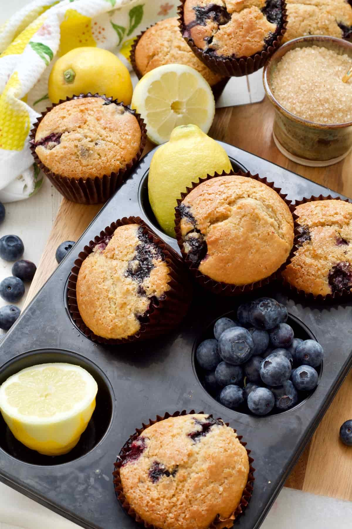 Muffin tin with muffins, lemons and blueberries in it.