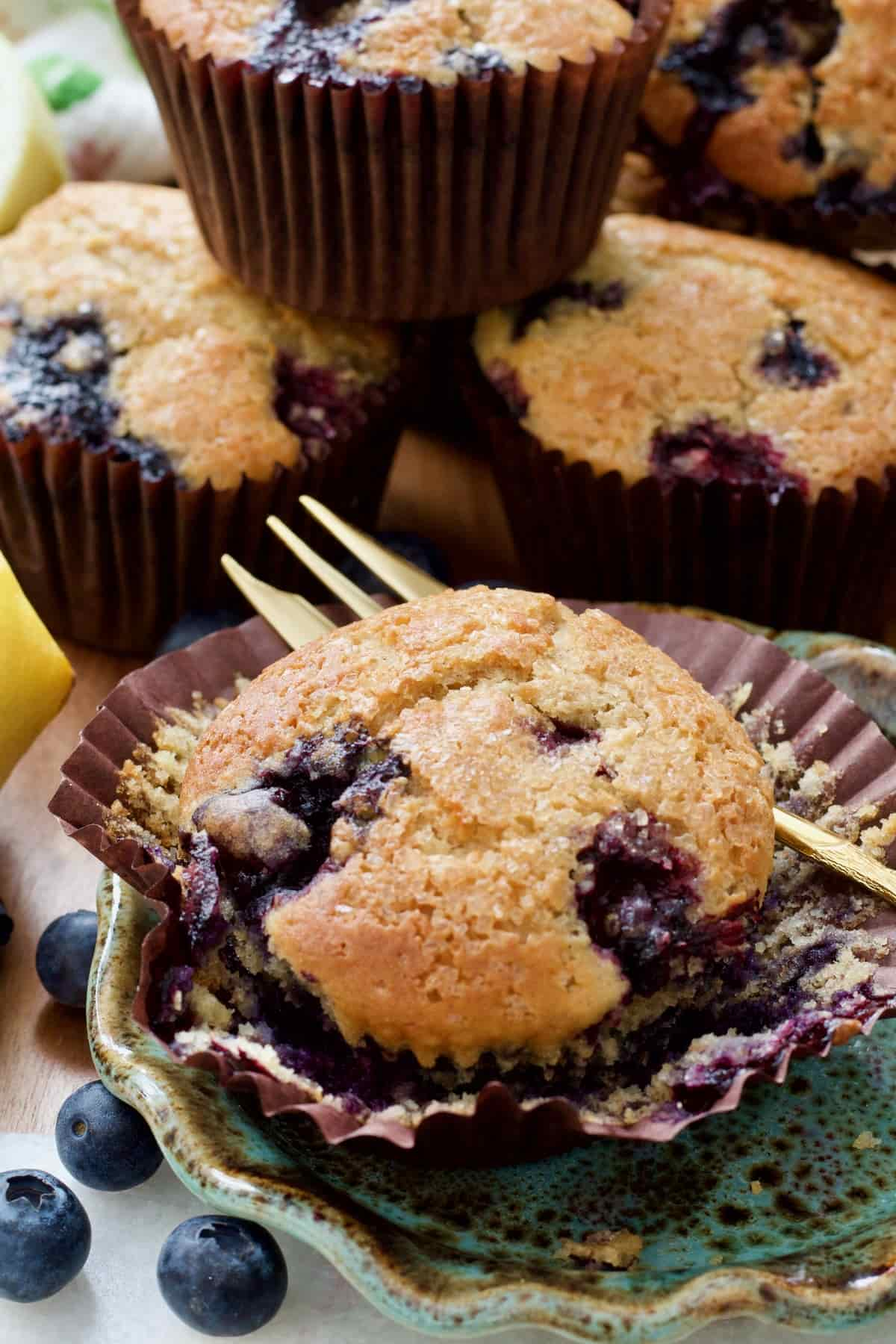 Blueberry muffin on a wrapper with a fork.