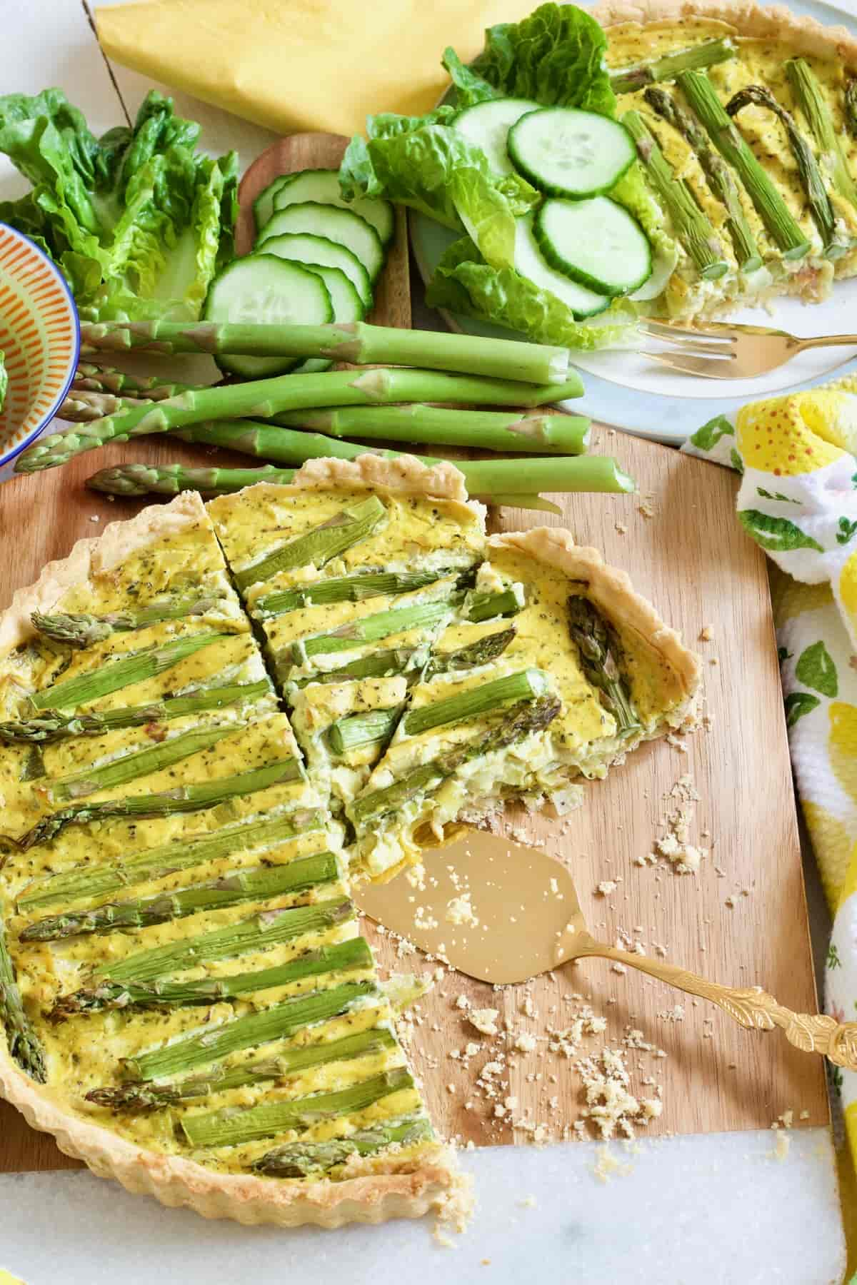 Cut vegan quiche on a board with crumbs.