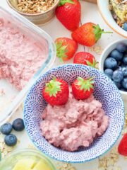 Breakfast spread, bowl with strawberry overnight oats & 2 strawberries.
