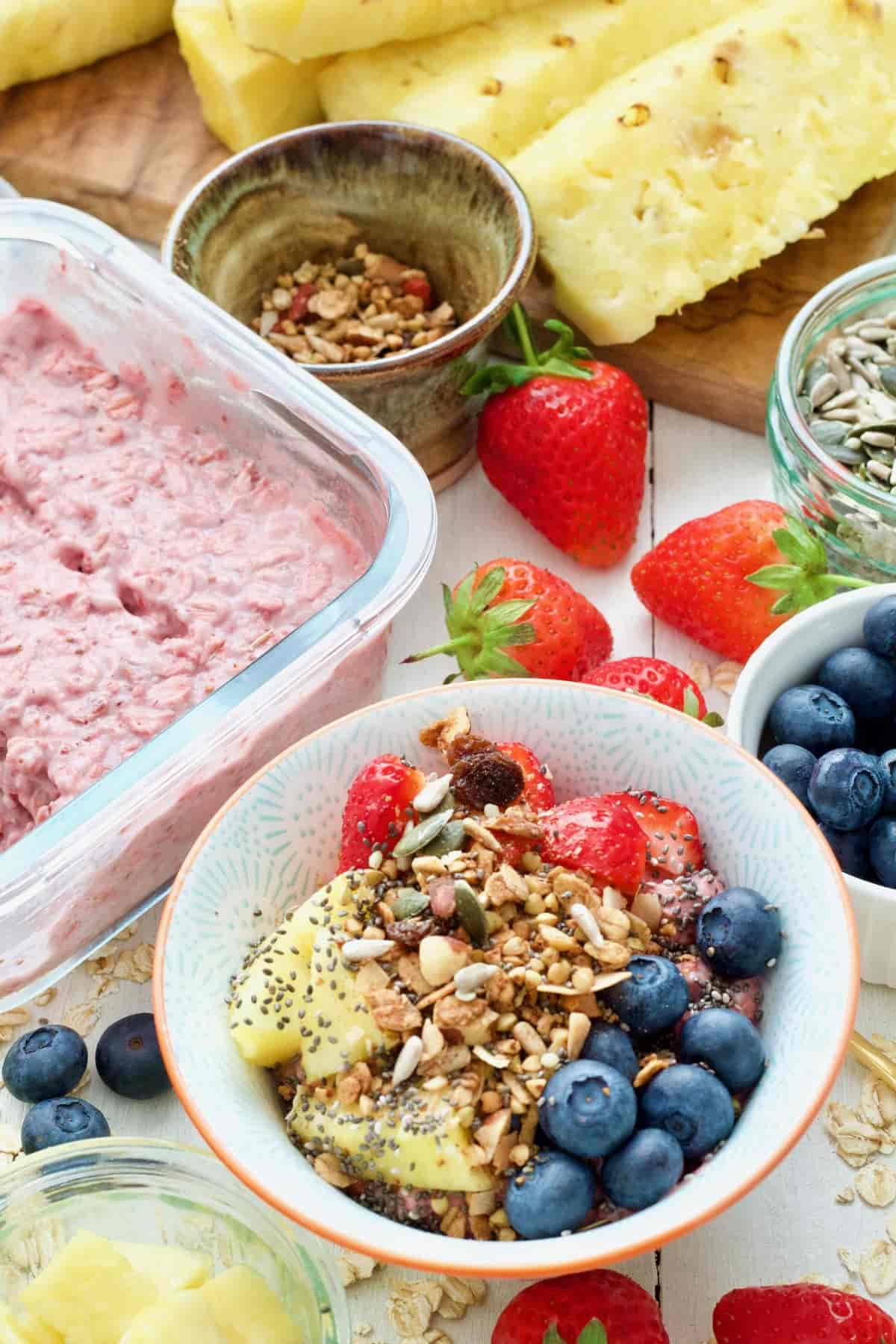 Strawberry overnight oats in a bowl with toppings.