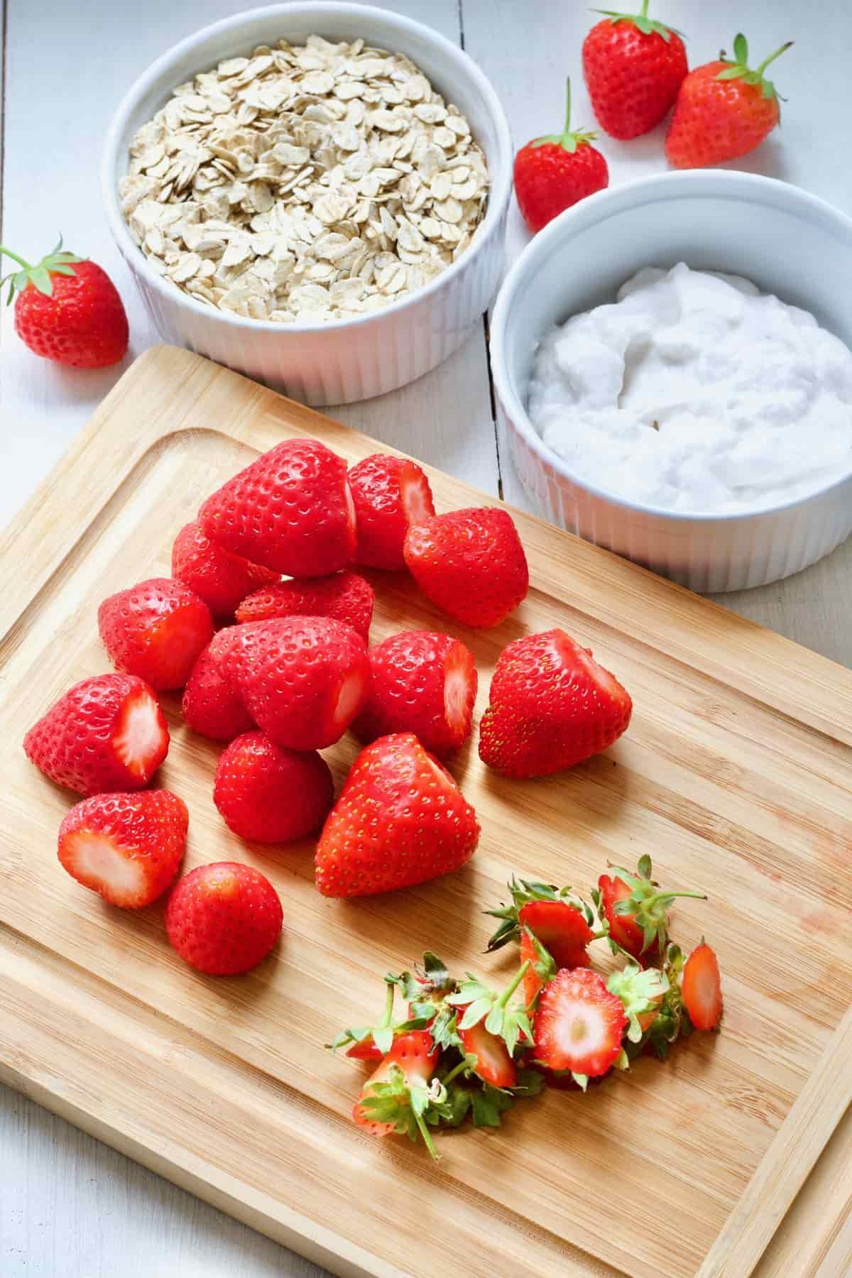 Hulled strawberries on a board, oats, yogurt.