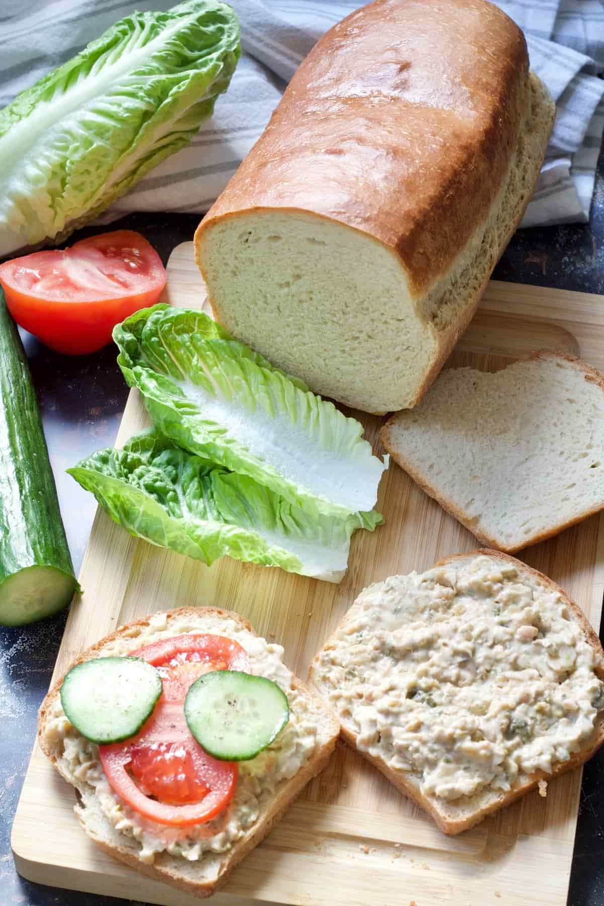 Sandwich in the making with lettuce & bread loaf on a board.