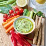 Bowl with broad bean dip, veg & crackers.