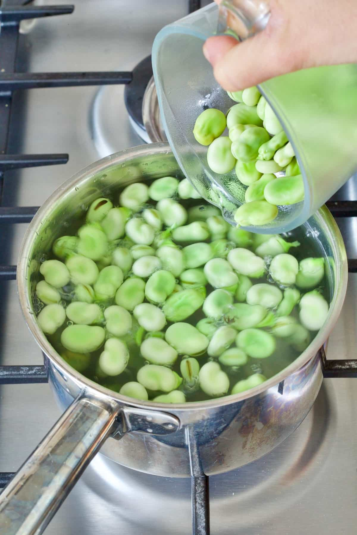 Raw broad beans being added to the pan with boiling water.