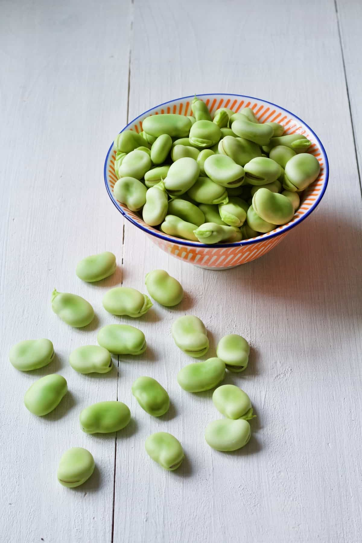Skinned, raw broad beans in a bowl with some on a board.