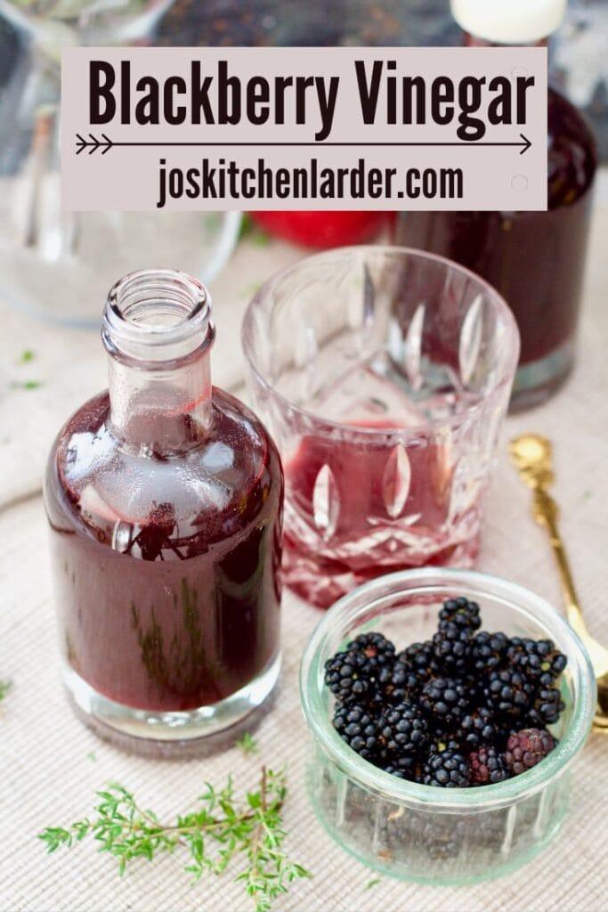 Bottles vinegar, tumbler and bowl with blackberries.