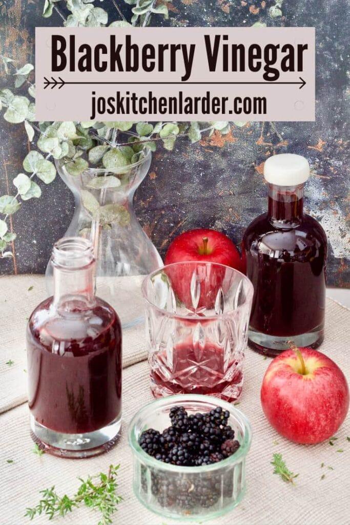 Bottles with vinegar, bowl of blackberries, apples.