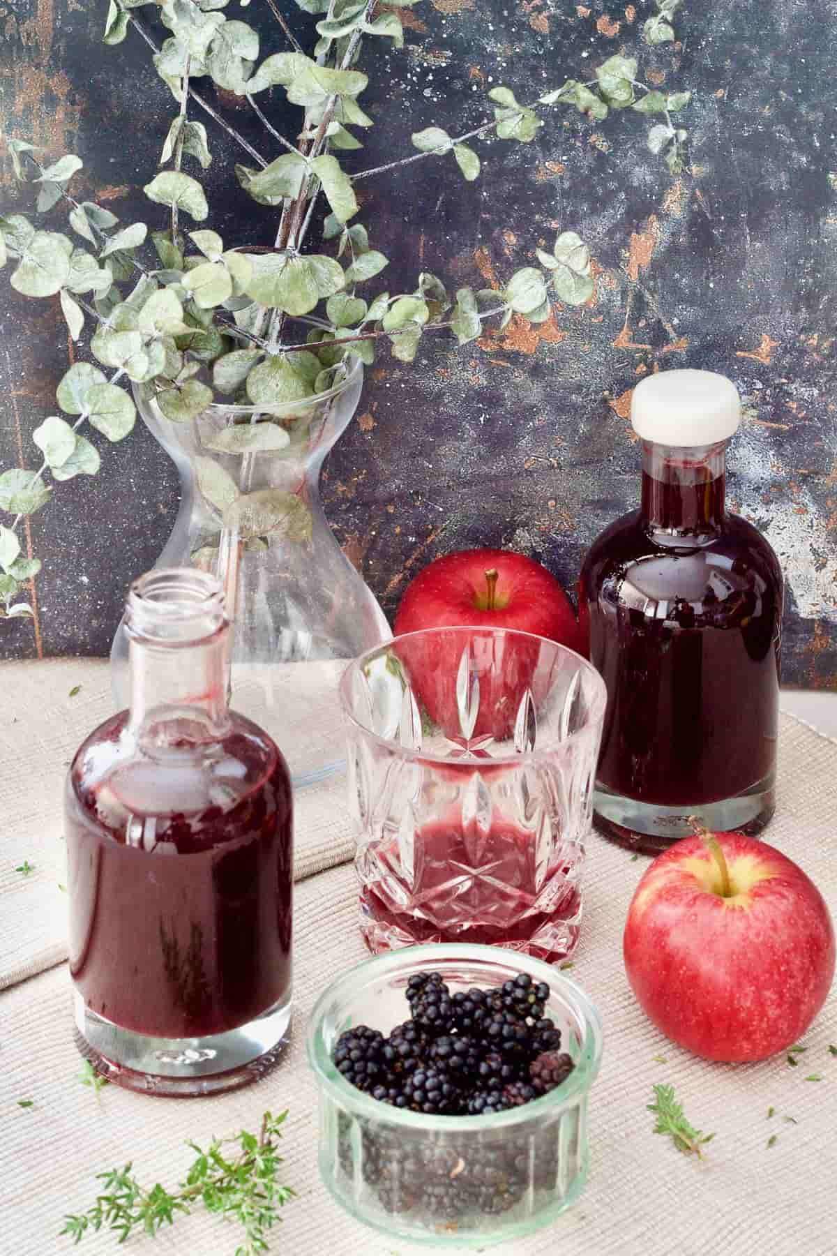 Bottles with vinegar, bowl with blackberries, tumbler and apples.