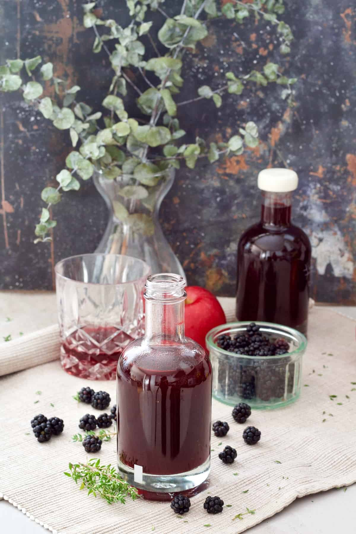 Open bottle of vinegar and scattered blackberries.