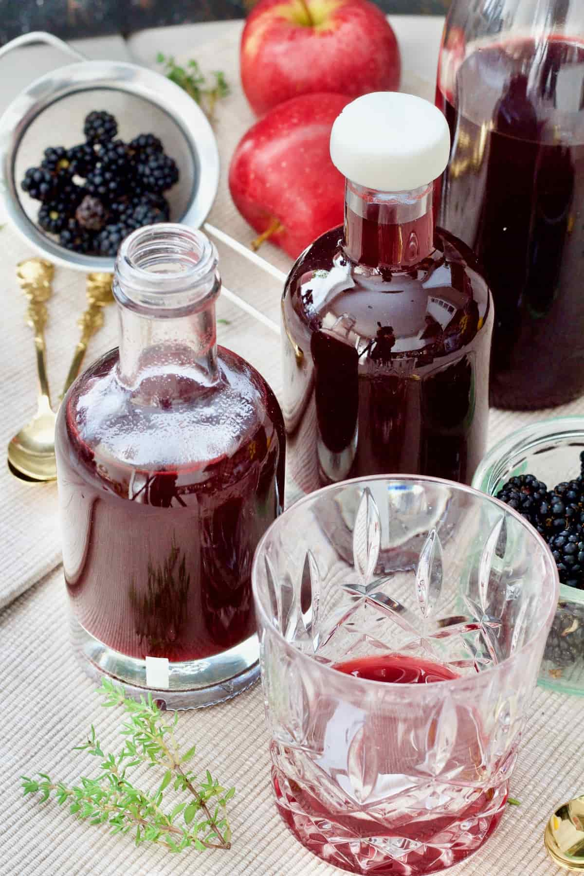 Two bottles of blackberry vinegar, small tumbler.