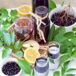Fresh elderberries, green leaves & juice in bottles & glasses.