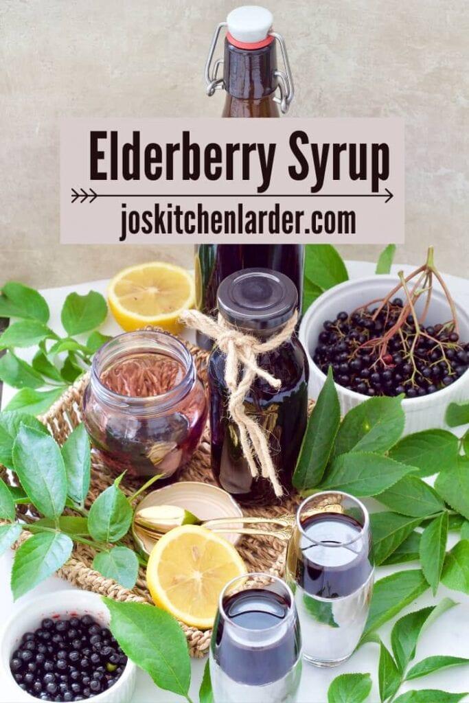 Elderberry syrup in bottles & shot glasses, fresh berries & leaves.