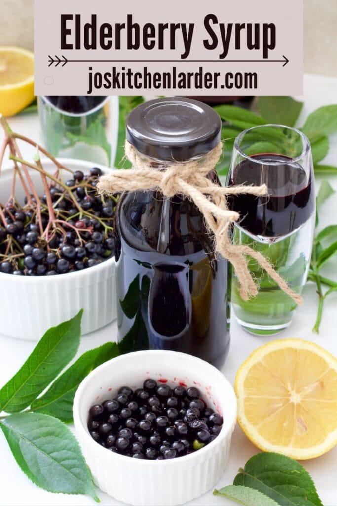 Small bottle & shot glass with elderberry syrup, fresh elderberries.