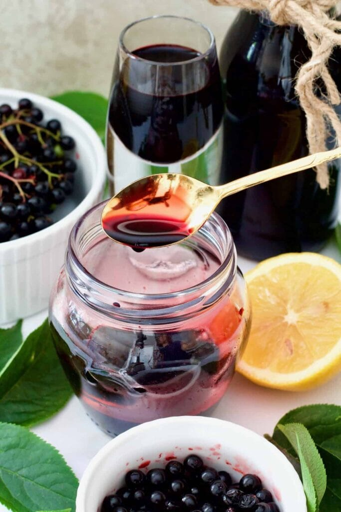 Elderberry syrup trickling off the spoon into a jar.