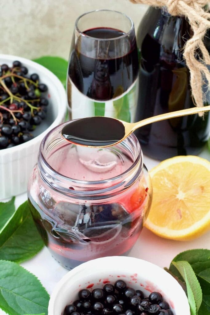 Spoonful of elderberry syrup over the jar.