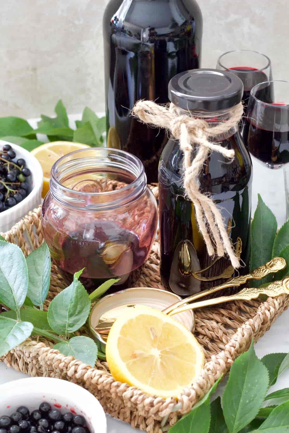 Open jar with elderberry syrup in a wicker tray.