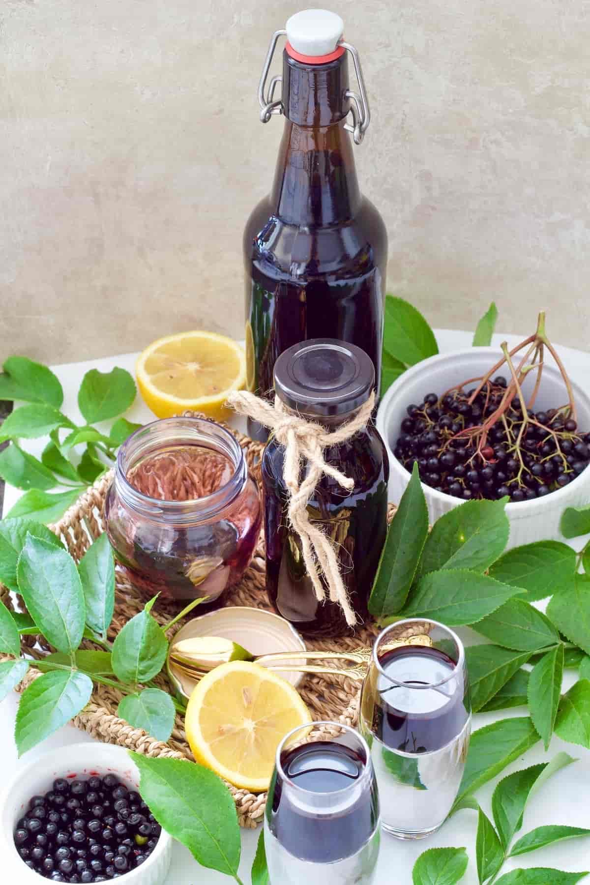 Fresh elderberries, leaves & syrup in bottles, jar & shot glasses.